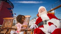 Young guest sits with Santa Claus aboard Disney Cruise Line