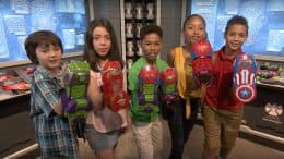A group of kids show their custom built Super Hero Gauntlets at Super Hero Headquarters in Disney Springs