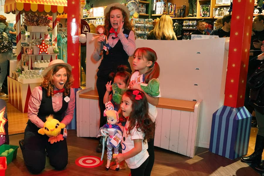Cast member at a Disney Store locations playing a game with a guest