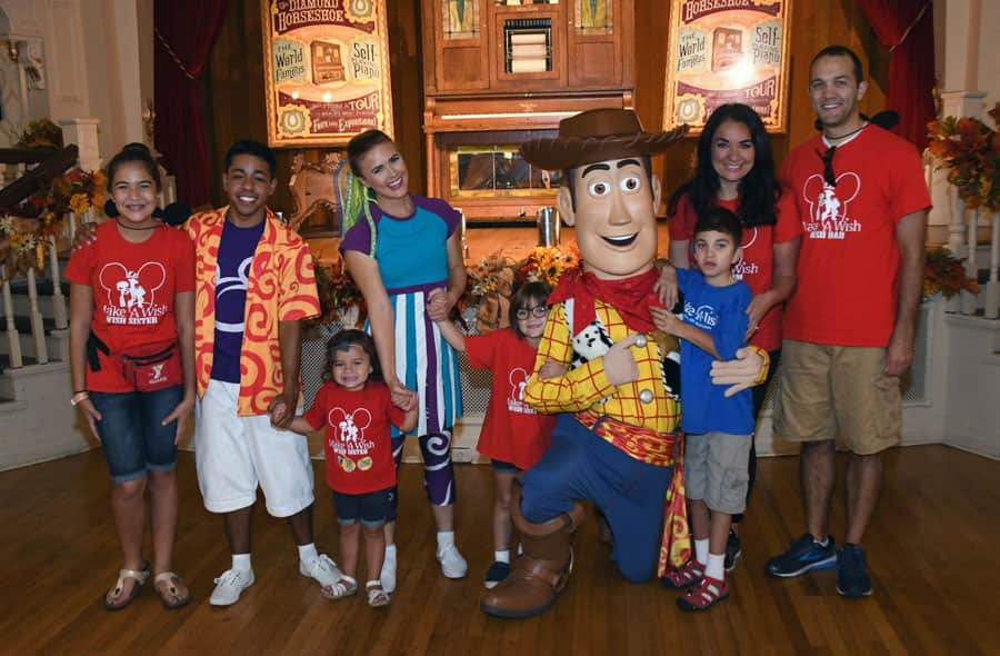 Nine-year-old Grant and his family pose with Woody and one of the Move it! Shake it! MousekeDance it! Street Party team during Grant's Make-A-Wish trip