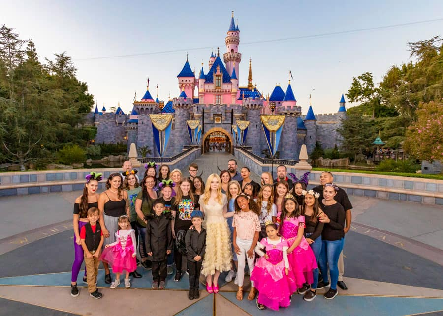 Actress Elle Fanning poses with fans in front of Sleeping Beauty Castle at Disneyland park