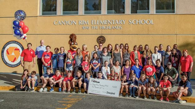 Jason Smith, director of Planning and Industrial Engineering at Disneyland Resort and alongside Disney Ambassador Justin Rapp pose with Canyon Rim Elementary School faculty, staff, students, PTA board members and parents on the school's campus