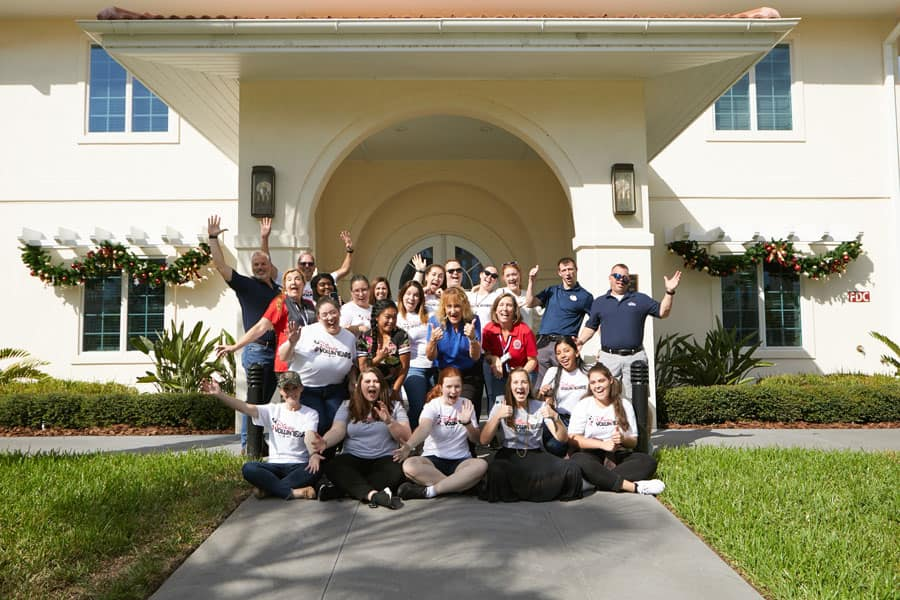 Group of Walt Disney World cast members pose in front of Orlando Fisher House after decorating for the holiday season
