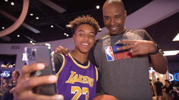 Teen Reece Henry takes a photo with former NBA player Quentin Richardson at the NBA Experience at Walt Disney World Resort