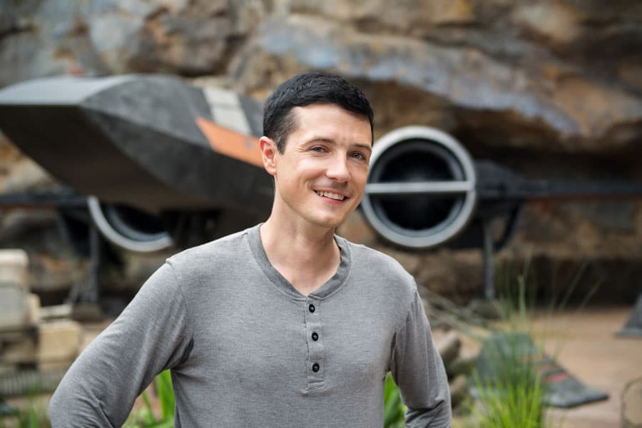 Matt Martin, Creative Executive of Franchise Story & Content from the Lucasfilm Story Group stands in front of Poe's X-wing from Star Wars: Rise of the Resistance