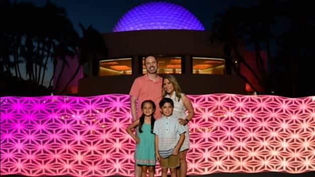 Family poses at Disney PhotoPass location in Future World near Spaceship Earth at Epcot