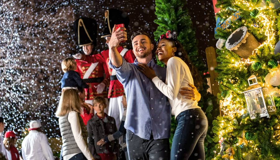 Guests take a photo and explore the Disney Springs Christmas Tree Trail