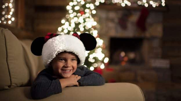 Child wearing a Santa Mickey hat in front of a Christmas Tree