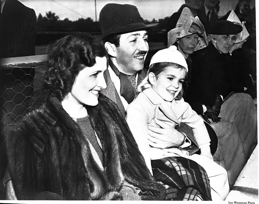Lillian, Walt, and Diane Disney watch the Rose Parade in 1939