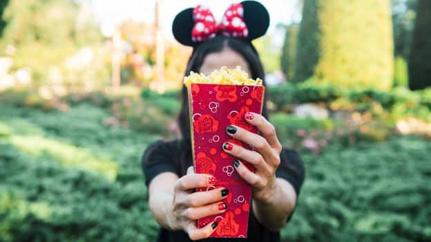 Woman wearing Minnie Mouse headband holds Disney popcorn bucket