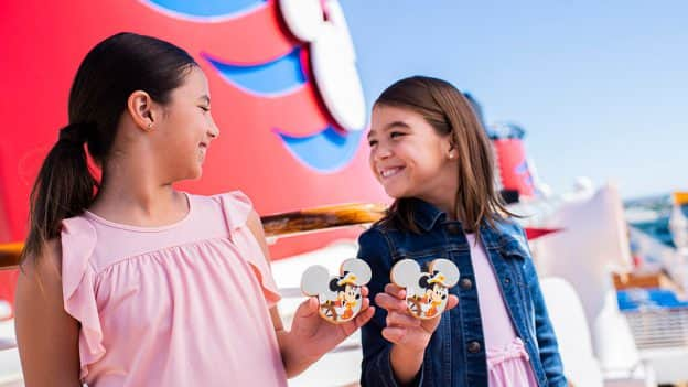 Two girls with Captain Minnie Mouse and Captain Mickey Mouse Cookies aboard Disney Cruise Line