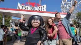 Guests pose with Edna Mode in front of the Incredicoaster at Disney California Adventure park