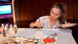 Disney Cruise Line Crew Member paints a mural panel