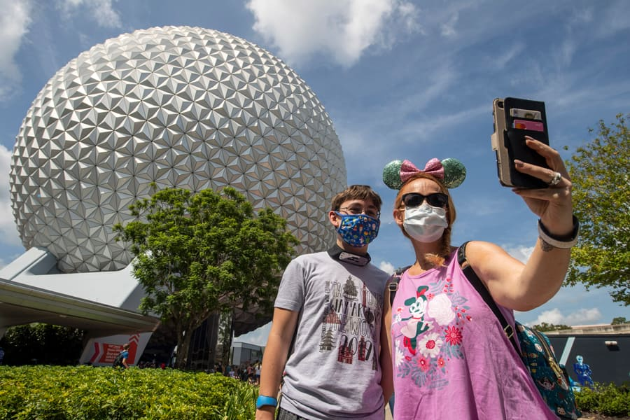 Guests take a selfie in front of Spaceship Earth at EPCOT