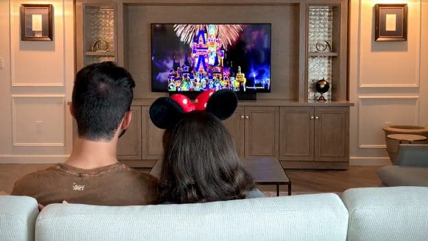 Couple watching fireworks in a Walt Disney World Resort hotel room