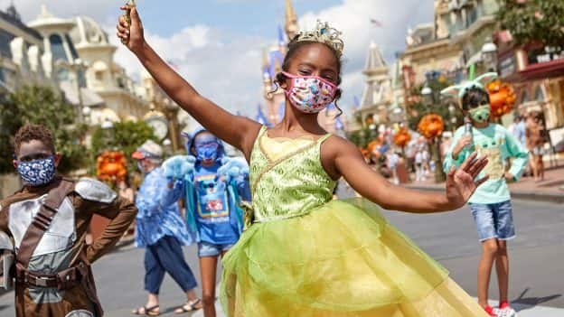 Kids wearing Halloween costumes and matching face coverings at Magic Kingdom Park