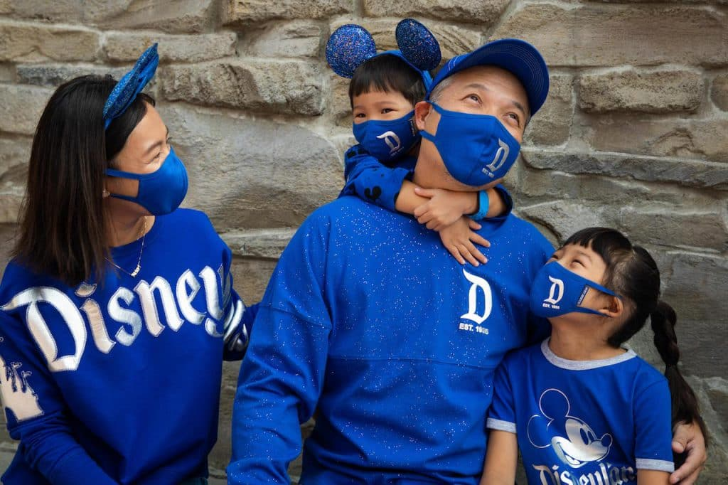 Family in the new Wishes Come True Blue Collection with Disneyland Resort logo