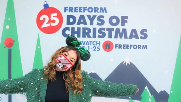 Guest in front of Freeform's '25 Days of Christmas' Photo Wall at Disney Springs