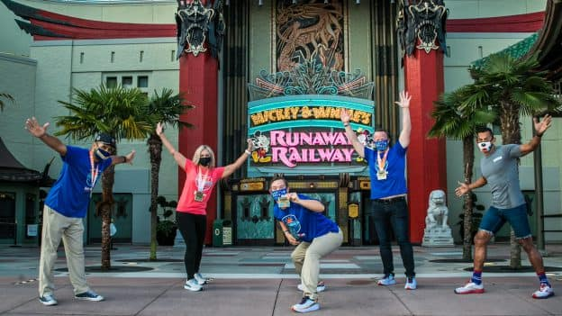 Ironman athlete Chris Nikic poses with cast member Jennifer Sturgess and friends in front of Mickey & Minnie's Runaway Railway at Disney's Hollywood Studios