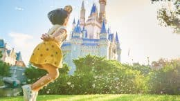Girl running in front of Cinderella Castle