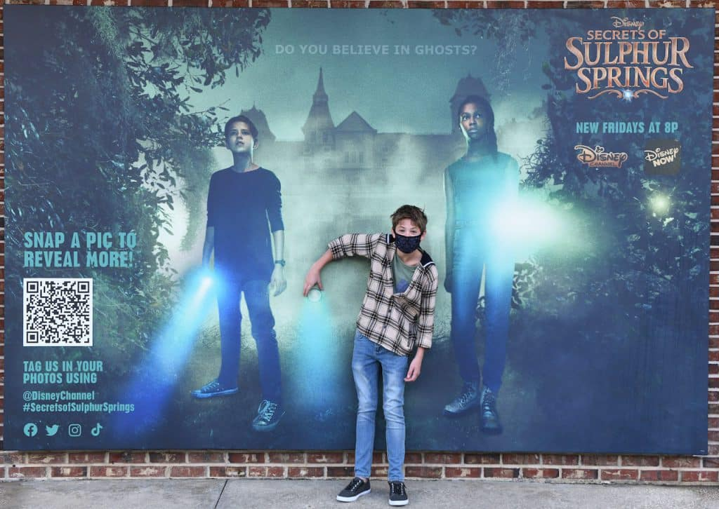 Preston Oliver from Disney's 'Secrets of Sulphur Springs' at the photo wall at Disney Springs