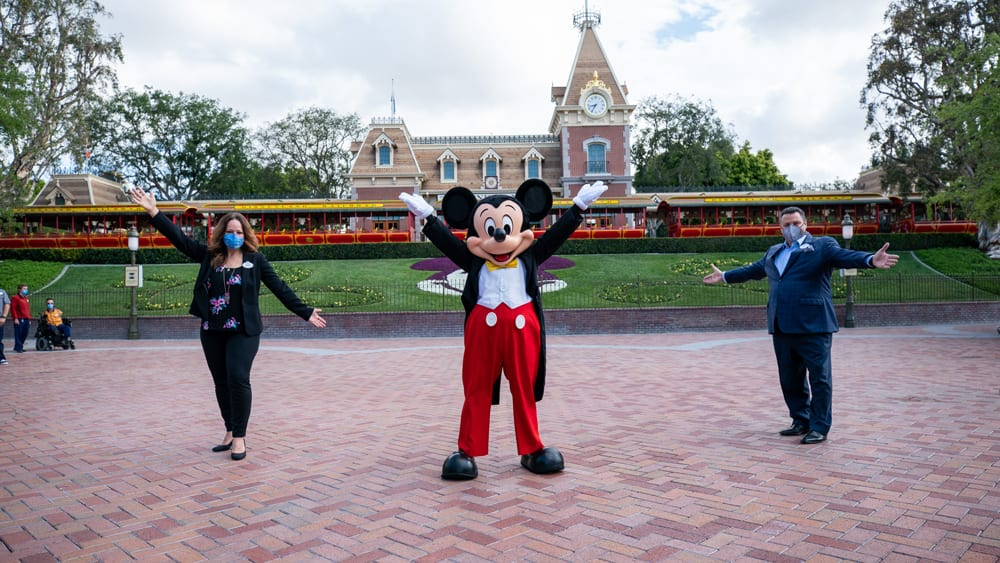 Mickey Mouse and two cast members at Disneyland park