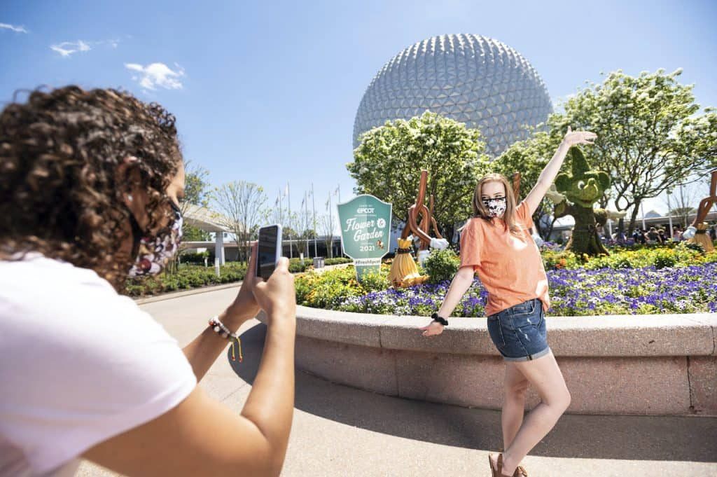 Guests taking a photo at the entrance of EPCOT