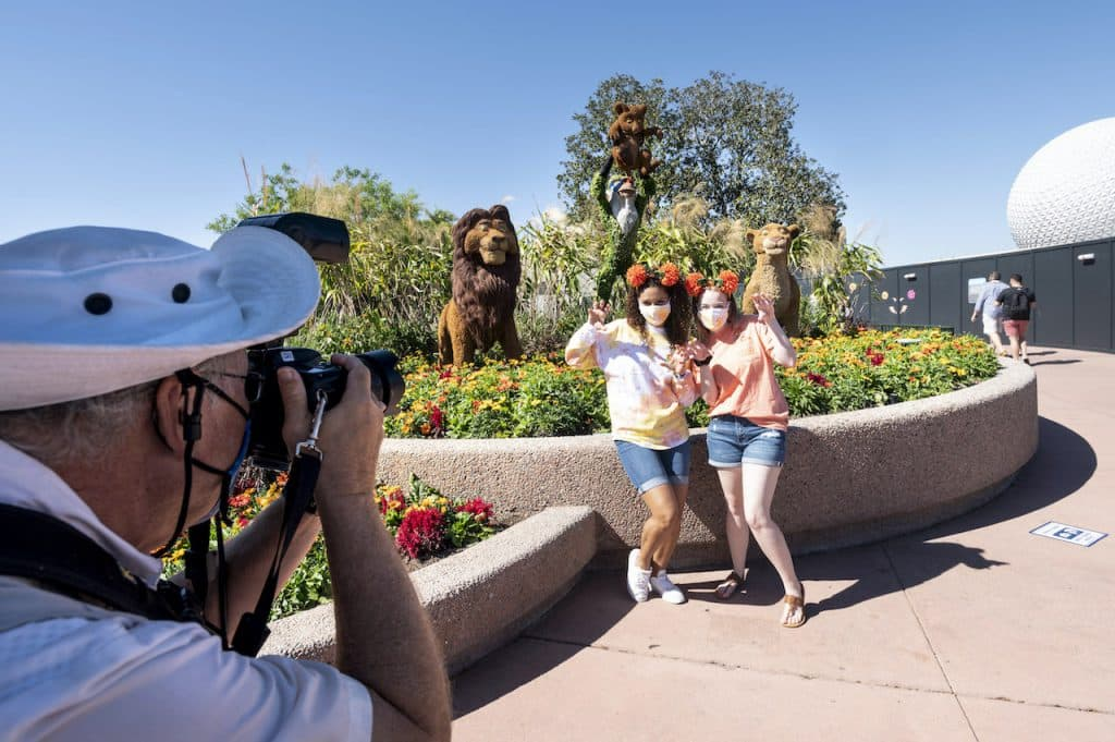 "Guests taking a photo in front of ""The Lion King"" topiary at the Taste of EPCOT International Flower & Garden Festival"