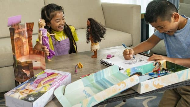 Girl playing with Disney Dolls and boy coloring