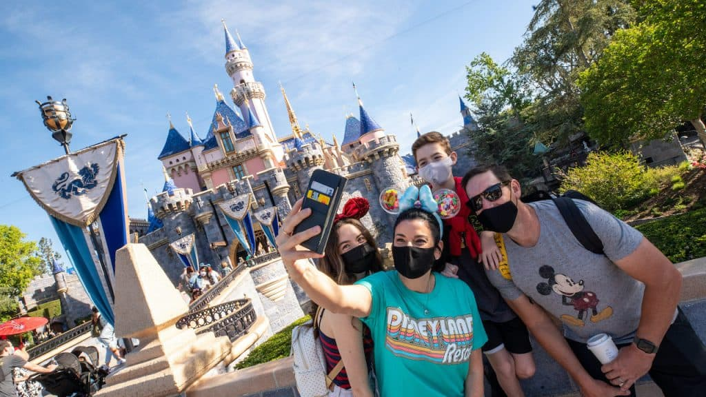 Guests pose in front of Sleeping Beauty Castle as Disneyland Park in Anaheim, California, reopens on Friday, April 30, 2021