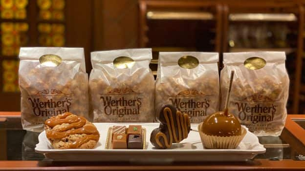 Bags of popcorn alongside a cookie, caramel flight, Mickey Mouse-shaped treat and caramel apple from Karamell-Küche at EPCOT