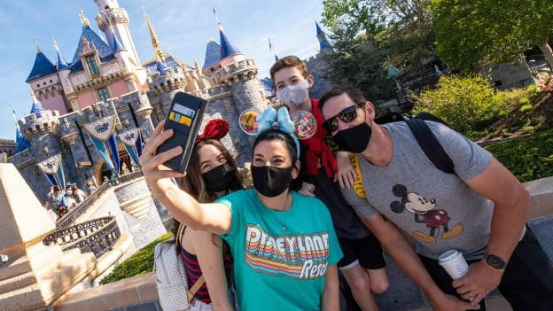 Guests take a selfie in front of Sleeping Beauty Castle at Disneyland park