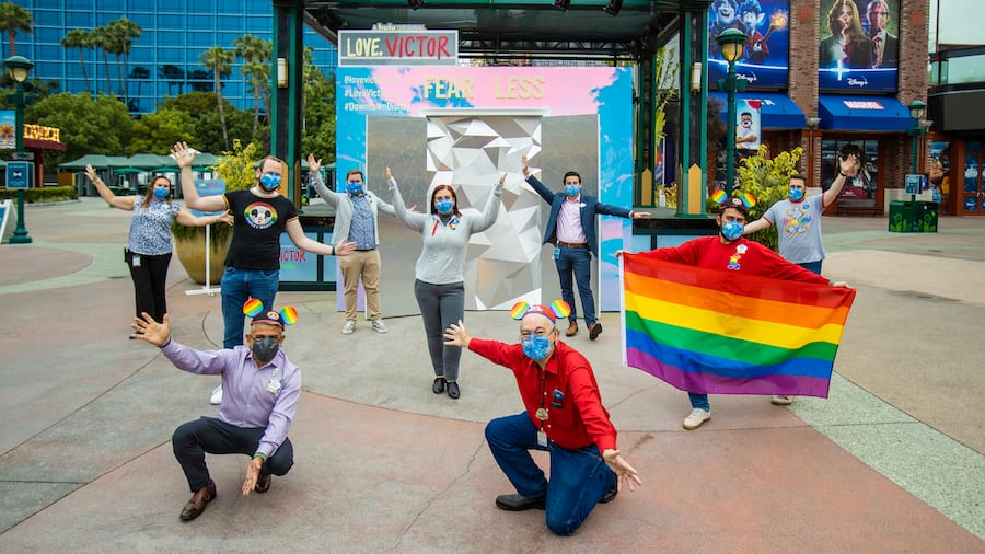 """Members of the Disney PRIDE group posing in front of the """"Love, Victor"""" photo activation in the Downtown Disney District"""