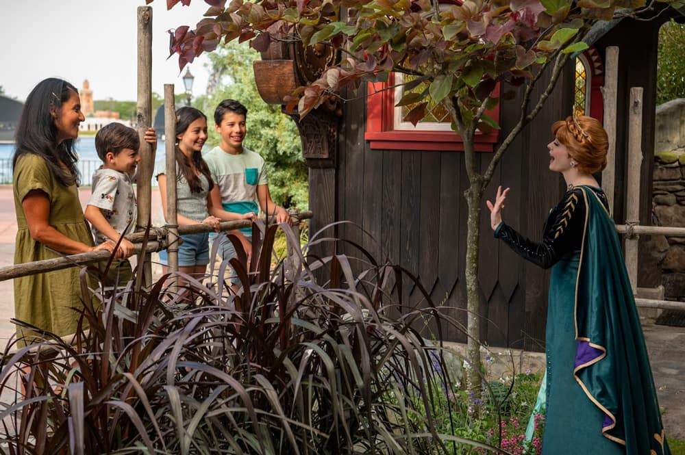 Family interacting with Anna at Frozen Ever After