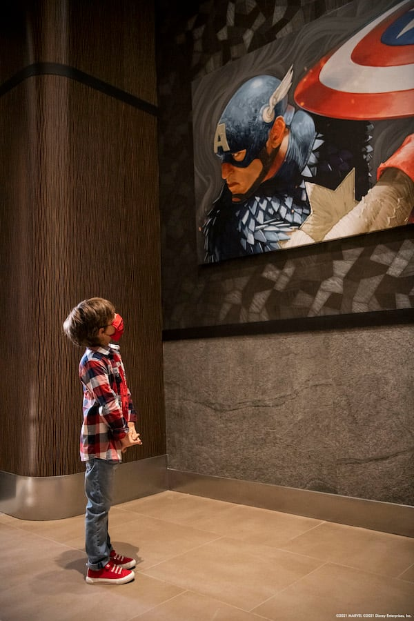 Boy looking at a portrait of Captain America in Disney's Hotel New York –The Art of Marvel