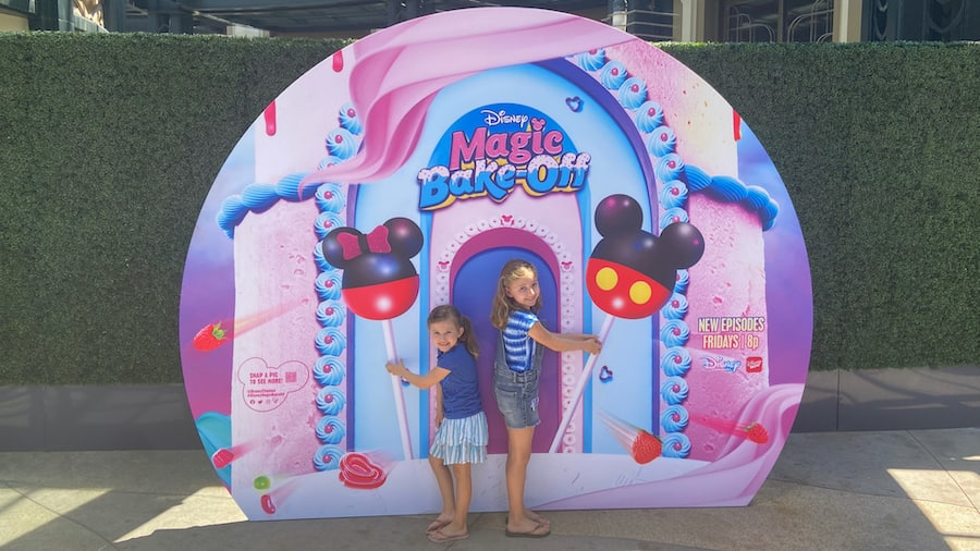 """Girls with the """"Disney's Magic Bake-Off"""" photo wall at the Downtown Disney District"""