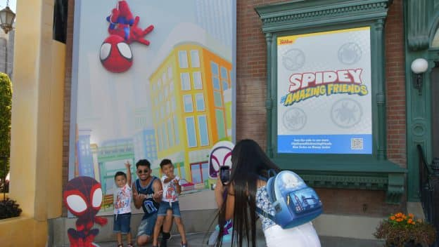 """Guests take a photo at the """"Spidey and his Amazing Friends"""" photo wall in Hollywood Land in Disney California Adventure park"""