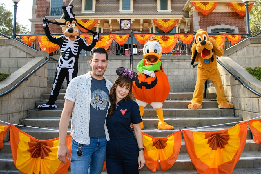 Zooey Deschanel and Jonathan Scott pose with Goofy, Donald and Pluto in their Halloween finest at Disneyland Park