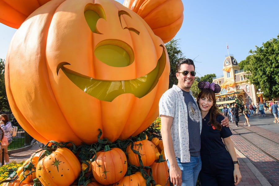 Jonathan Scott and Zooey Deschanel pose with the Mickey Mouse jack-o'-lantern on Main Street, U.S.A. at Disneyland Park
