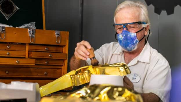Cast member adds gold detail to decor at Magic Kingdom Park