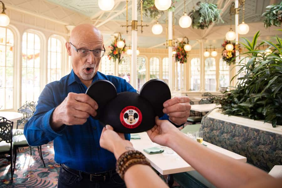 A cast member is presented with a Mickey Mouse ear hat.