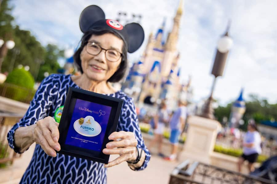 A cast member displays her new nametag in front of Cinderella Castle.