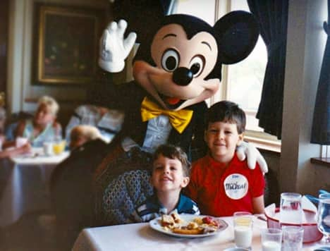 Young Steven and his brother, Michael, confer with Steven's future boss aboard the Empress Lilly Character Breakfast in Walt Disney World Village, c. 1990.