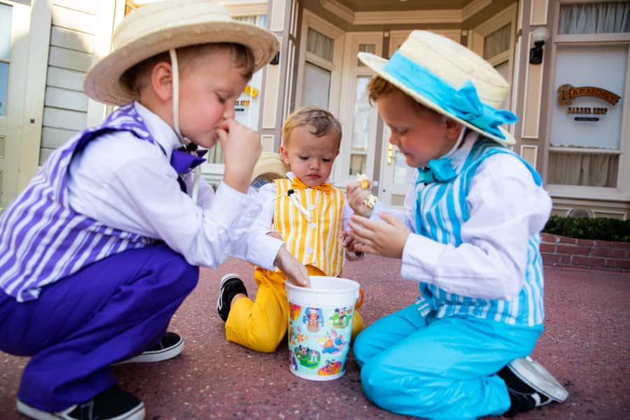 Young guests dressed as the Dapper Dans eat popcorn at Magic Kingdom Park on Oct. 1, 2021, on the 50th anniversary of Walt Disney World Resort