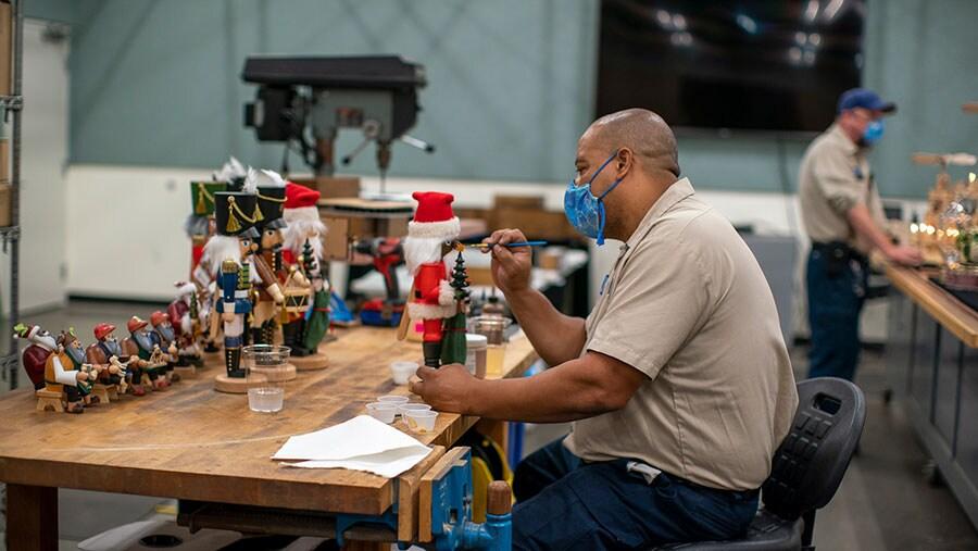 Cast member applying paiting details to nutcracker decoratoins