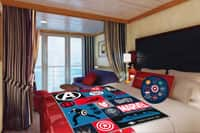 A Disney Cruise Line stateroom with an Avengers pillow and blanket on the bed