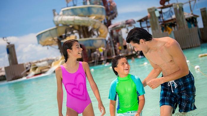 Un papá y sus 2 niños ríen juntos en el agua frente al área de juegos acuáticos en Castaway Cay