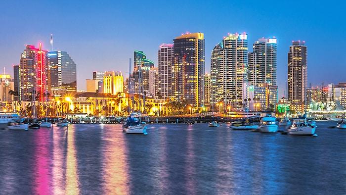 La orilla del mar de una gran ciudad con modernos edificios durante la noche