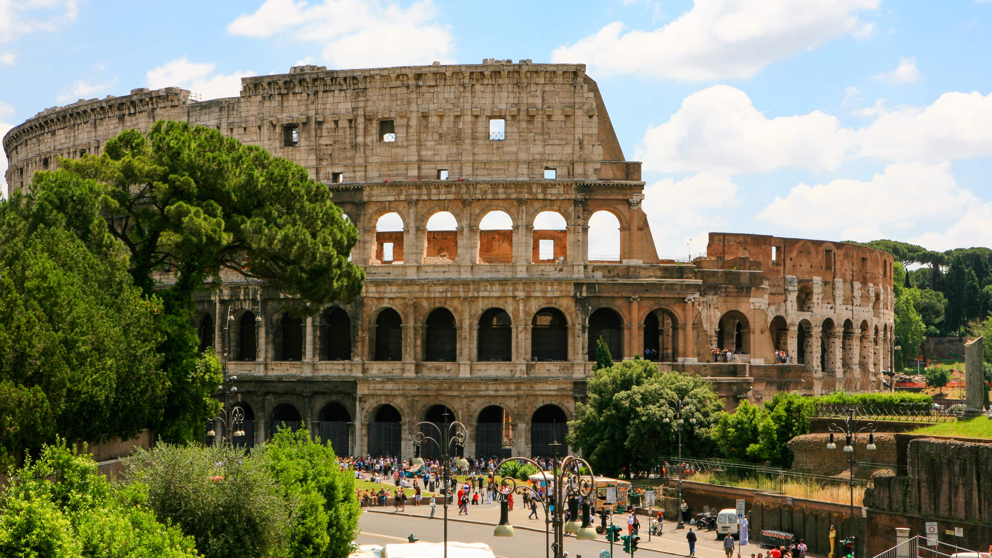 Pessoas caminham do lado de fora das ruínas do Coliseu, em Roma