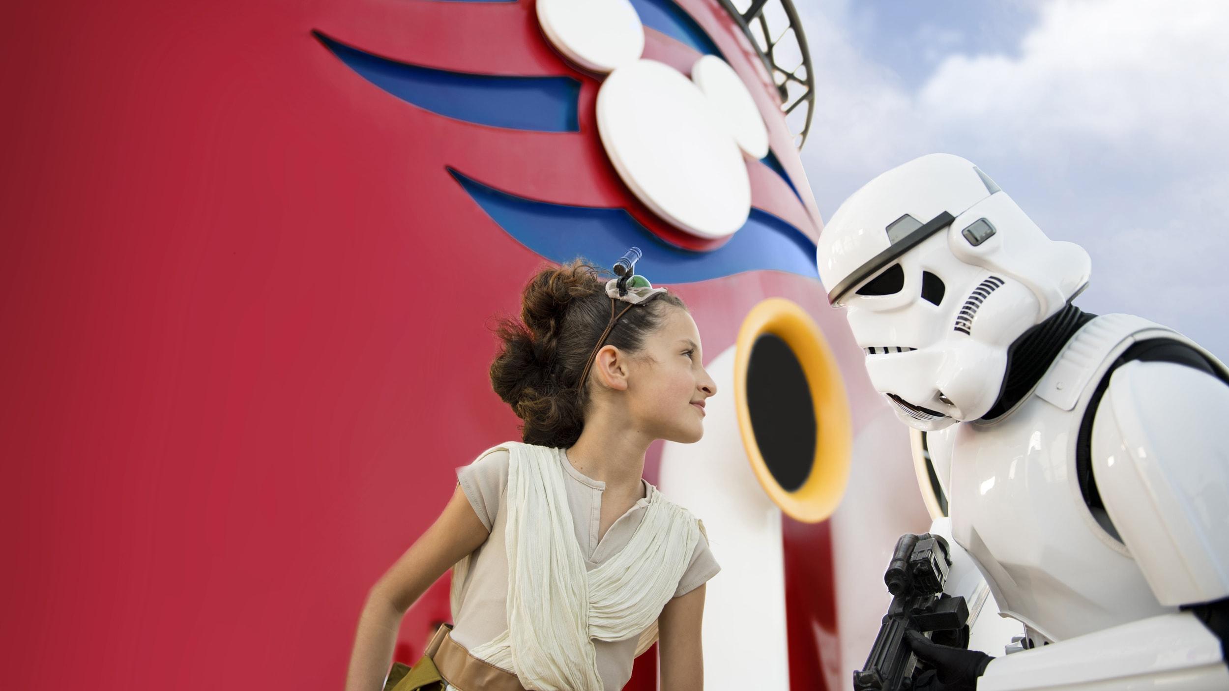 Uma garota vestida como a Rey, de Star Wars, encara um stormtrooper a bordo de um navio da Disney Cruise Line.